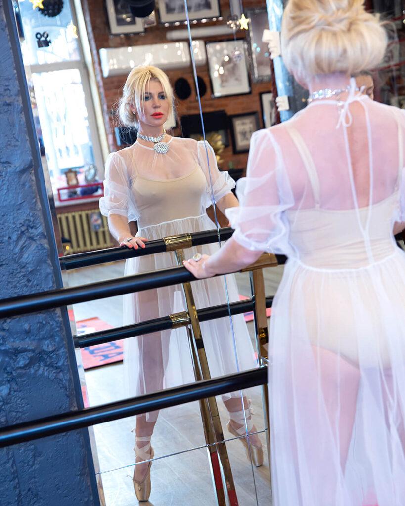 Урок боди балета в Adornos Center. На фото - женщина в процессе выполнения упражнений перед зеркалом.